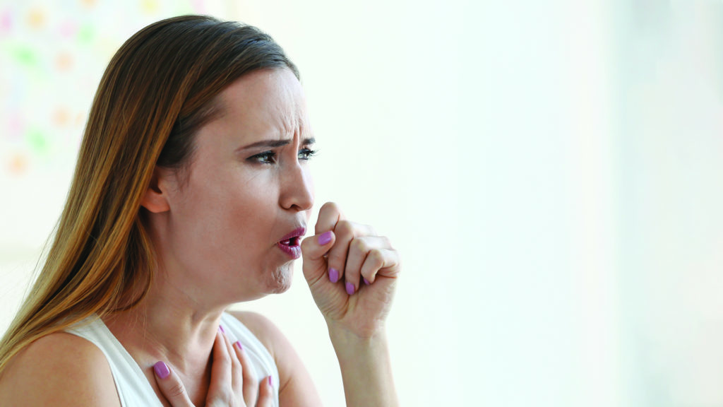 Lung cancer signs and symptoms - woman coughing